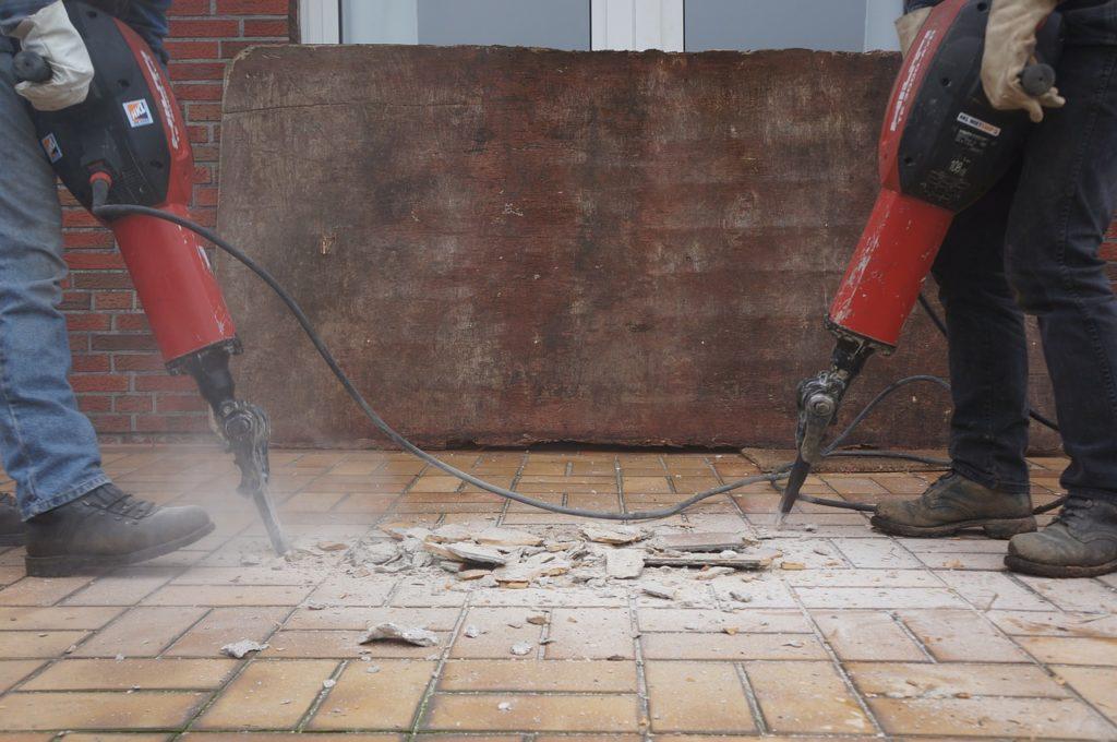 שני פועלי הריסה מבצעים קידוח עם קונגו ברצפה